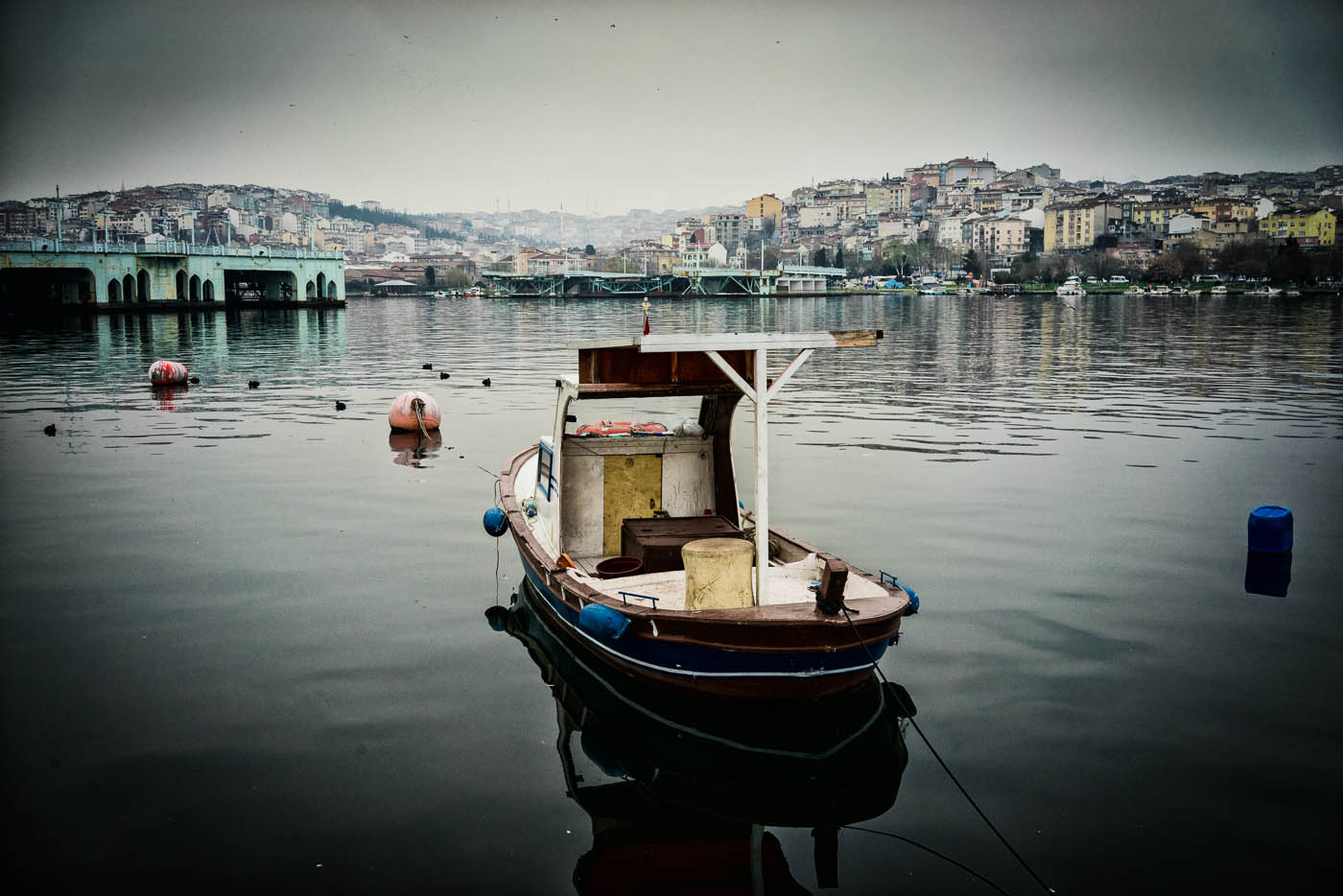 Small fisherman boat on the Golden Horn by old Galata bridge in Istanbul
